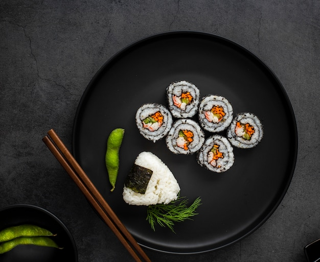 Flat lay maki sushi with rice and chopsticks