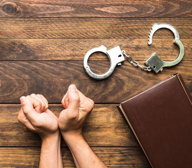 Flat lay man pleading guilty with book and handcuffs
