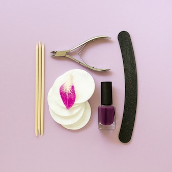 Flat lay of manicure accessories with nail polish on a lilac table