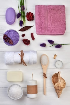 Flat lay many spa accessories on white wooden desk