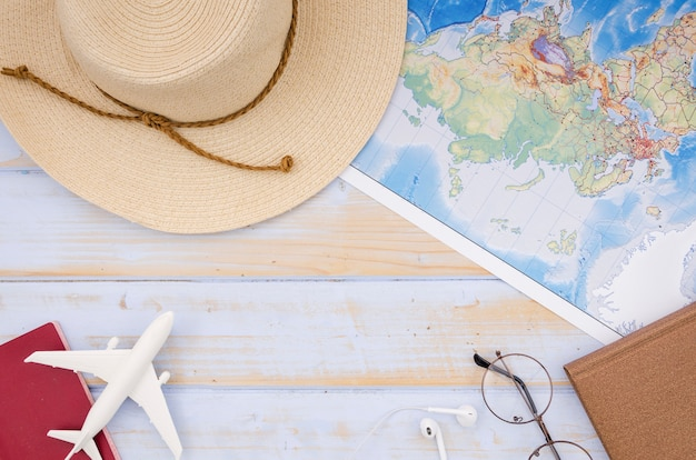 Flat lay of map and hat on wooden table