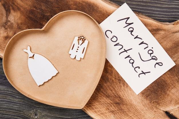 Плоская концепция брачного контракта. коробка в форме сердца и костюмы жениха и невесты.