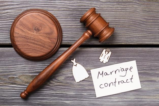 Плоская концепция брачного контракта. деревянный молоток с миниатюрными свадебными костюмами на виде сверху.