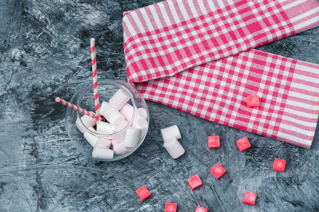 Flat lay marshmallows and sugarcanes in jar with candies and red gingham tablecloth on dark blue marble surface. horizontal