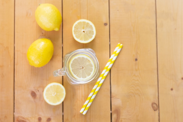 Flat lay. mason glass jar with water , fresh lemons and straws on wooden table. summer time vacation holiday.