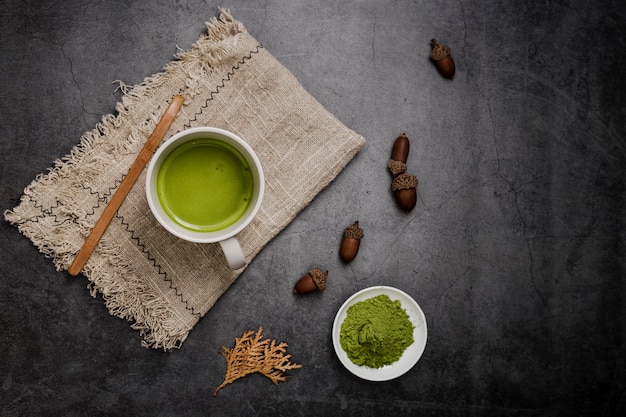 Flat lay of matcha tea in cup and acorns