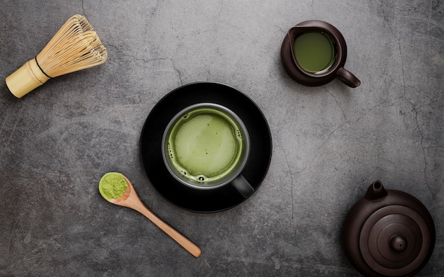Flat lay of matcha tea in cup on plate with bamboo whisk