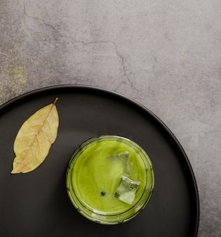 Flat lay of matcha tea glass with ice cubes