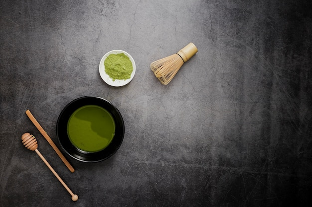 Flat lay of matcha tea with bamboo whisk and honey dipper