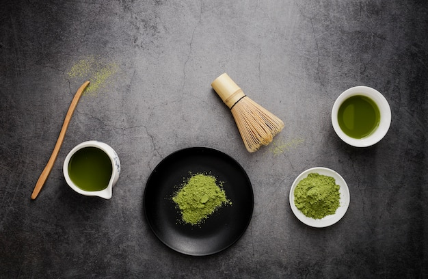 Flat lay of matcha tea with bamboo whisk and plate