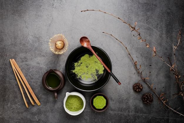 Piatto disteso di tè matcha con cucchiaio e rami di legno