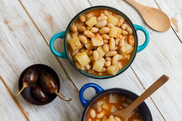 Flat lay meal with beans and potatoes in pot