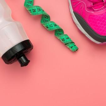 Disposizione piatta del metro a nastro con bottiglia d'acqua e scarpe da ginnastica