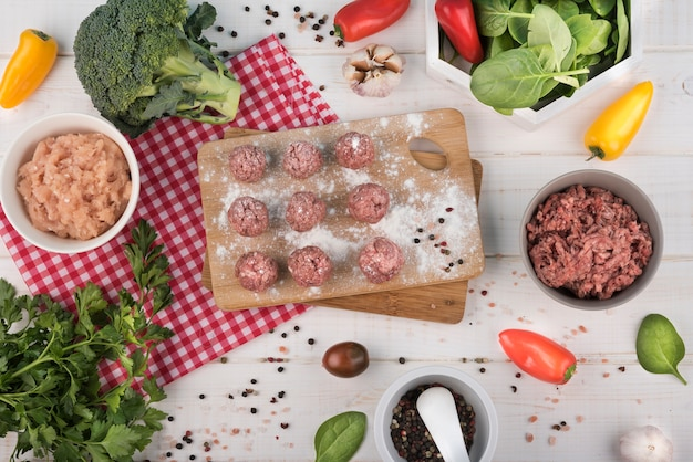 Flat lay meatballs on wooden board, minced meat and broccoli