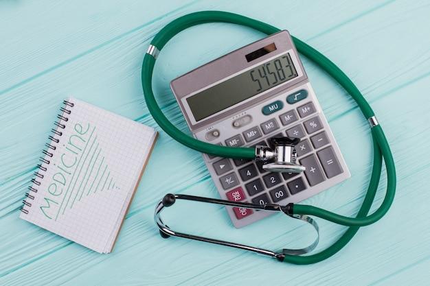 フラットレイ医療用組成物。青いパステルカラーの背景に電卓メモ帳聴診器。