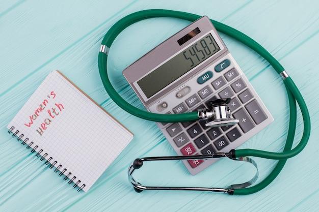 フラットレイの医療用組成物には、青いパステルカラーの背景に電卓のメモ帳聴診器が含まれています。上面から。