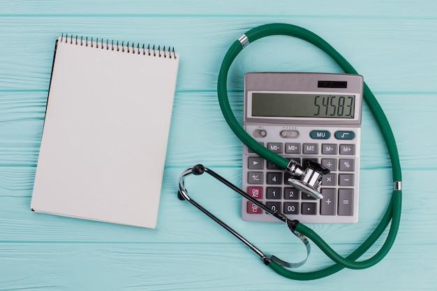 フラットレイの医療用組成物には、青いパステルカラーの背景に電卓のメモ帳聴診器が含まれています。白い空白のメモ帳。上面から。