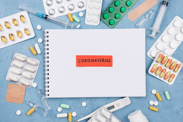Flat lay medical elements composition with coronavirus tag on notepad