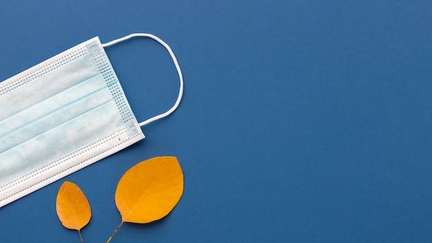 Lay piatto di mascherina medica con foglie di autunno e copia spazio