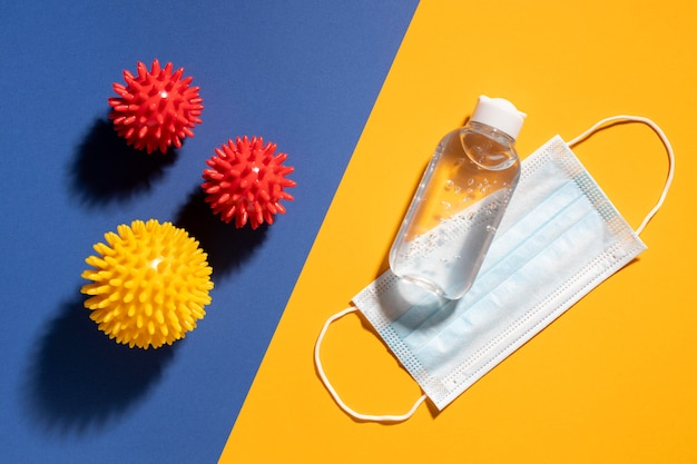 Flat lay of medical mask with hand sanitizer and viruses