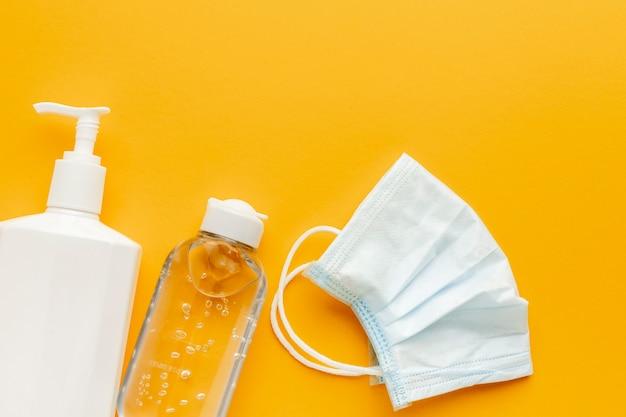 Lay piatto della maschera medica con bottiglia di liquido e disinfettante per le mani