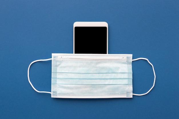 Lay piatto della mascherina medica con lo smartphone