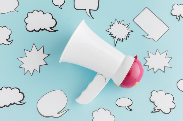 Flat lay of megaphone with chat bubbles