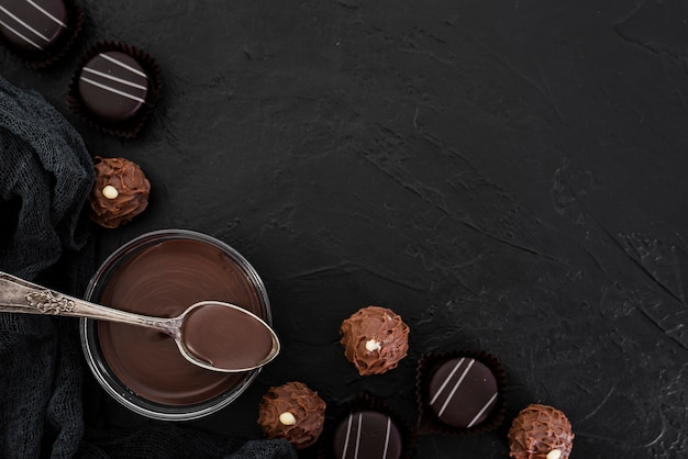 Flat lay melted chocolate and candies with copy space