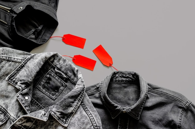 Flat lay of men black clothes with red price tags on gray background for black friday shopping sale concept.
