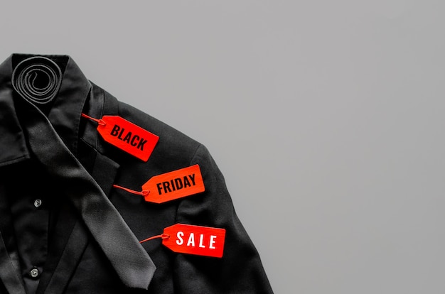 Flat lay of men black color shirt, suit, necktie and red price tags on gray background for black friday sale concept.