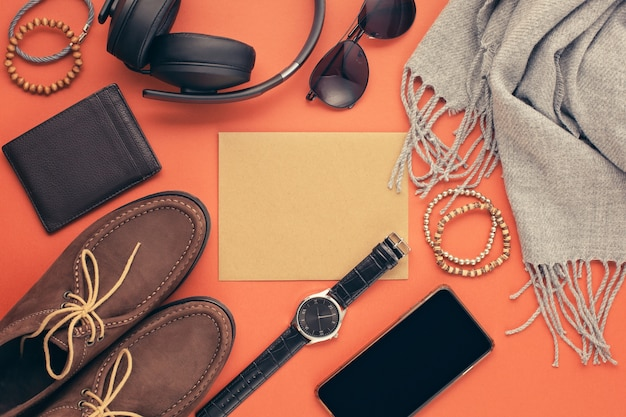 Flat lay of men's accessories with shoes, watch, phone, earphones, sunglasses, scarf over the orange