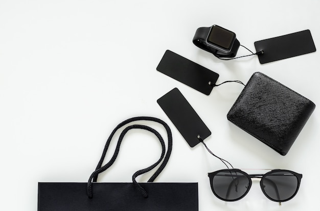 Flat lay of men stuffs - black wallet, sunglasses, smart watch, price tags and shopping bag on white background for black friday sale concept.