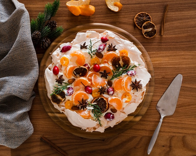 Flat lay of meringue cake decorated with orange slices and rosehip