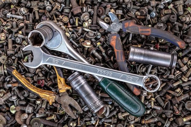フラットレイアウトメタルレンチ、ラチェット、ペンチ、さまざまなサイズの交換可能なツールヘッドは、さまざまな金属製の歯車、ネジ、釘、上面図の背景にあります。