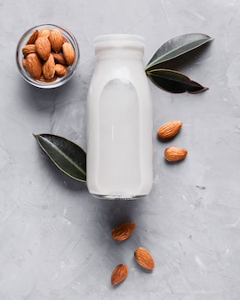 Flat lay milk bottle with almonds