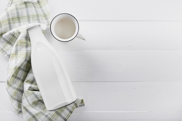 Flat lay milk bottle with cup on table
