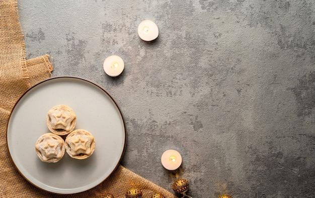 Disposizione piatta di torte tritate servite su un piatto e candele accese