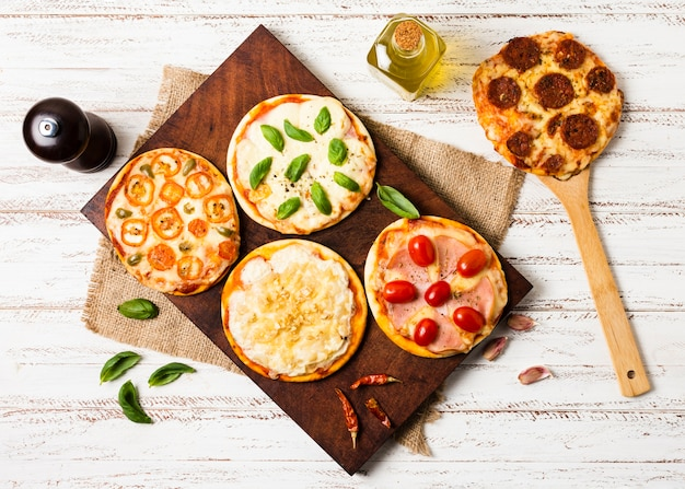 Flat lay of mini pizza on wood tray