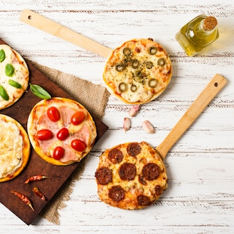 Flat lay of mini pizza on wooden tray
