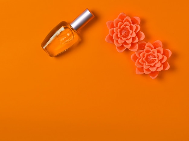 Flat lay minimalism of a perfume  bottle and candles in the form of flowers on orange.