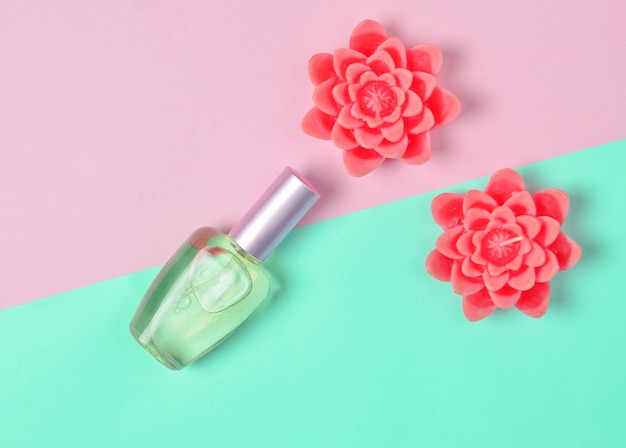 Flat lay minimalism of a perfume  bottle and candles in the form of flowers on a pastel.