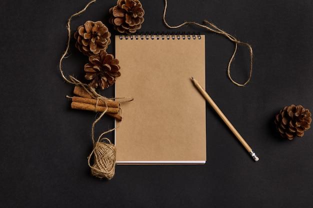 コピー広告スペース、シナモン、松ぼっくり、黒い背景の上に横たわっているロープと空の空白のシートでクラフトノートに木製の鉛筆のフラットレイミニマリストの構成。