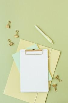 テキスト、ペン、緑のクリップのコピースペースと空白のシートクリップボードを備えたフラットレイミニマリストホームオフィスデスク
