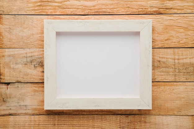 Flat lay minimalist white frame with wooden background