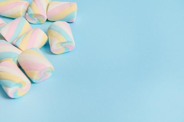 広告用のコピースペースを備えた青いパステルカラーの背景の隅にあるカラフルな甘いマシュマロのフラットなミニマルな構成。