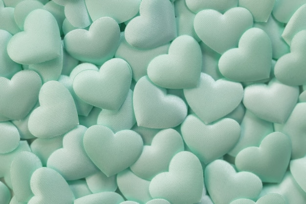 Flat lay of mint satin hearts background