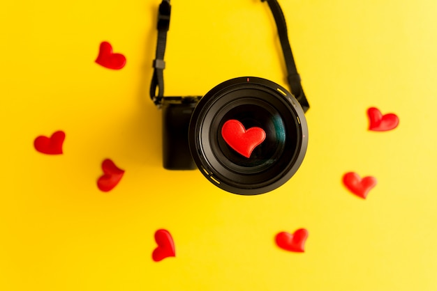 Flat lay of mirrorless camera with lens and love red hearts on yellow background
