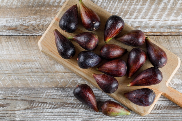 Flat lay mission figs in cutting board on wooden table. horizontal