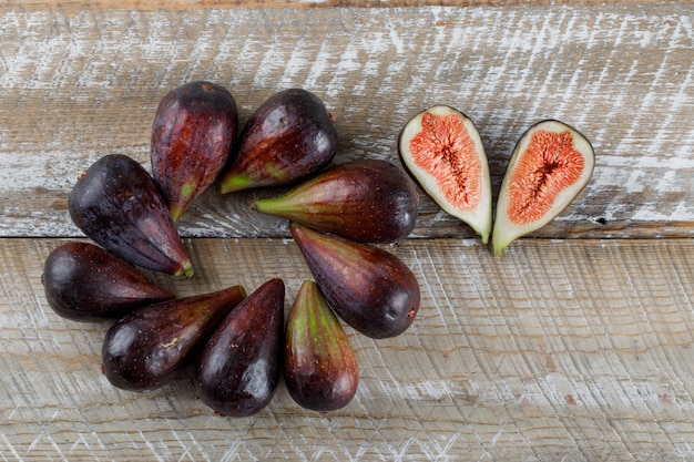 Flat lay mission figs with fig halves on wooden table. horizontal