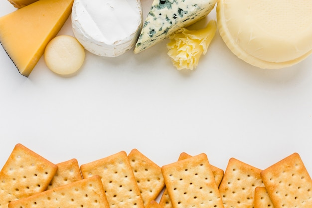 Flat lay mix of gourmet cheese with crackers